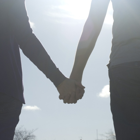 Two hands longing for each others warmth