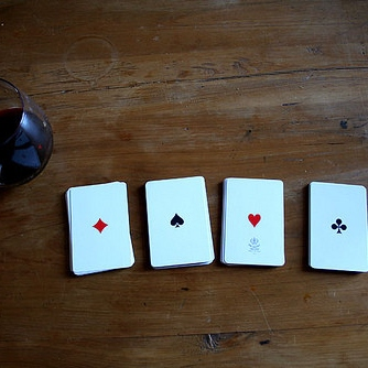 A deck of cards and a bottle of wine on a rainy Saturday night